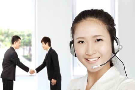 servicio al cliente: Sonriente mujer de negocios de servicios al cliente en el tel�fono Foto de archivo
