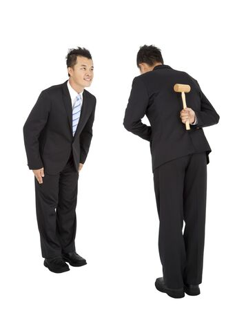 bowing: business competition concept.two asian businessman bowing and holding hammer behind
