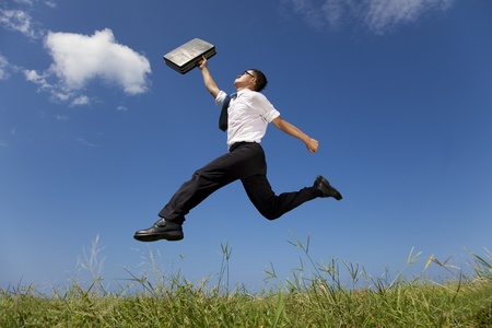 businessman running: happy businessman running over the grass field