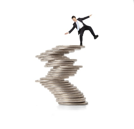 savings risk: financial and crisis concept. businessman standing on the unstable coins
