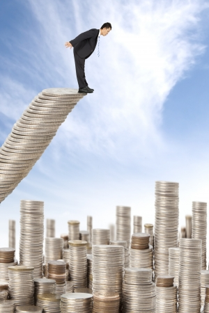 surprised businessman standing on the money stairs and watching many coin towers Stock Photo - 10960158