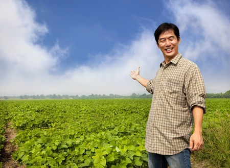 happy asian farmer showing his farm