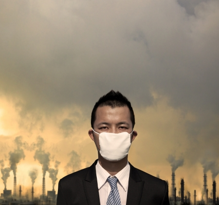 pollution: sad bussinessman with  mask and air pollution concept