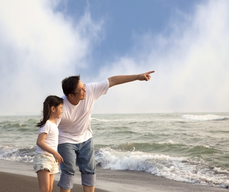 father pointing and little girl looking it on the beach photo