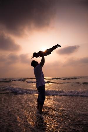 padres e hijos felices: la silueta de la familia feliz en la playa Foto de archivo