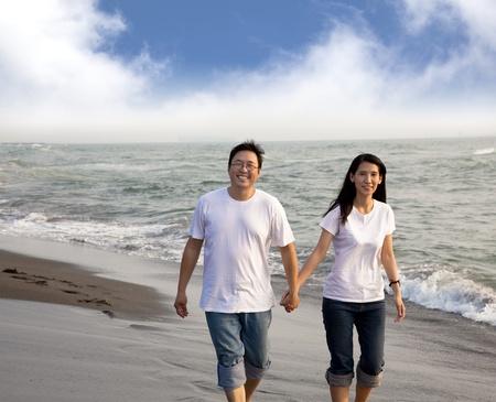 damas antiguas: feliz pareja de mediana edad caminando por la playa Foto de archivo