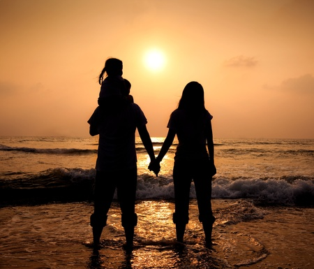 The silhouette of loving asian family walking while holding hands on beach at sunset photo
