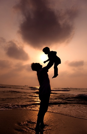 the silhouette of happy father and little girl on the beach photo