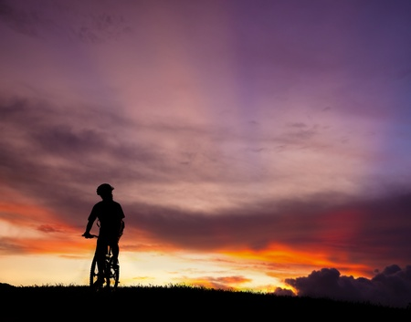 The silhouette of mountain bicycle rider on the hill with beautiful sunrise background Stock Photo