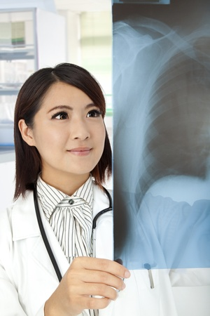 asian Doctor reviewing x-rays in doctor office photo