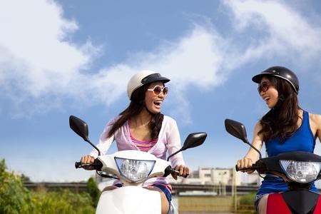 vespa: Niñas felices que viaje por carretera en una moto Foto de archivo