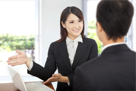 interacting: smiling Business woman showing at laptop and explaining a plan of work to client Stock Photo