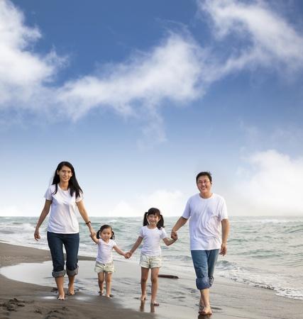Portrait de famille marchant sur la plage Banque d'images