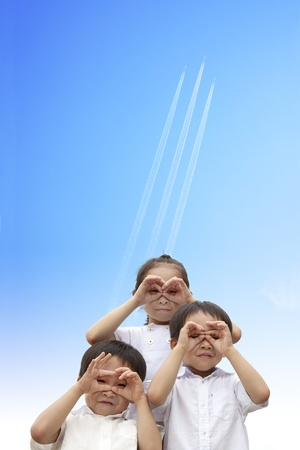 three happy kids watching the aircraft flying through to sky photo