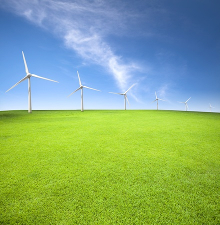 Wind turbines in an green field with cloud background photo