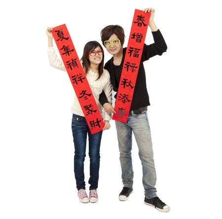 Happy chinese new year. Young couple holding  red spring couplets for lucky Stock Photo