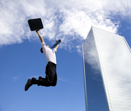 company: happy businessman jumping in front of a building