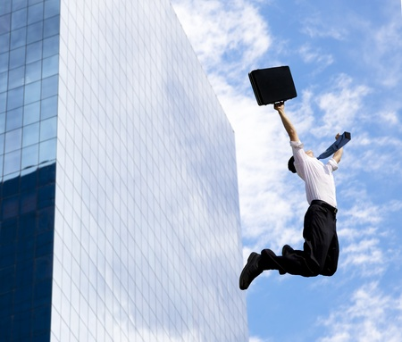 happy businessman jumping in front of a building photo