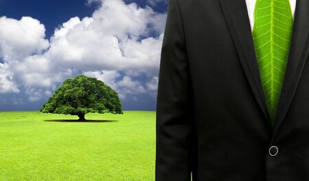 green business concept.Businessman with leaf tie and old tree background photo