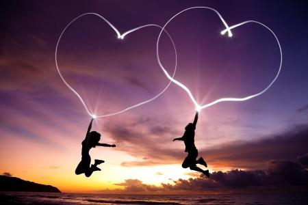 siluetas de enamorados: pareja de jóvenes saltando y dibujar corazones conectados con una linterna en el aire en la playa antes del amanecer Foto de archivo