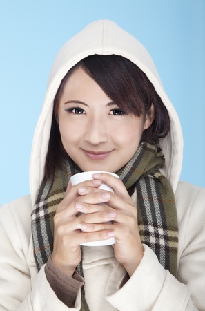 young woman wearing winter clothing and holding coffee cup  photo