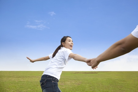 Happy young couple running on the  meadow Stock Photo - 11568002