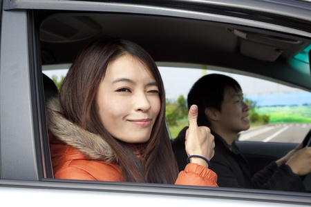 Happy smiling couple Driving in the car with thumbs up photo