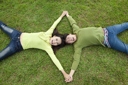 happy  asian couple lying on the grass photo