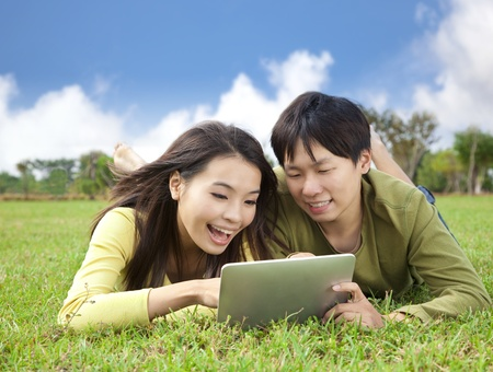 young asian student using tablet computer while lying in the park photo