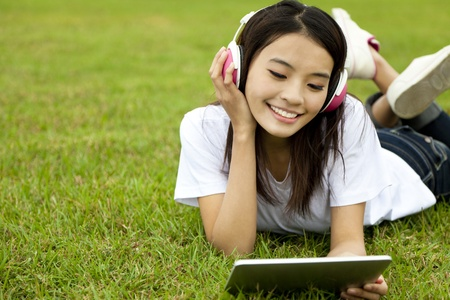 happy girl using tablet pc on the grass  photo