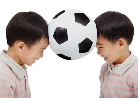 happy kids holding a football above their  head Stock Photo
