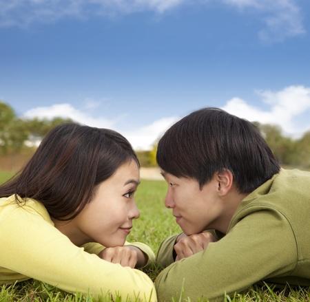 ni�as chinas: Feliz pareja de Asia tumbado en la hierba con fondo de nubes