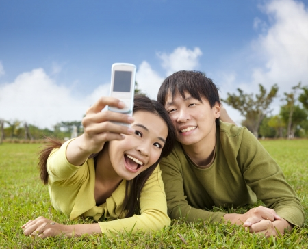 university life: asian couple taking photo by smart mobile phone