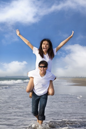 happy couple running in the water at the beach photo