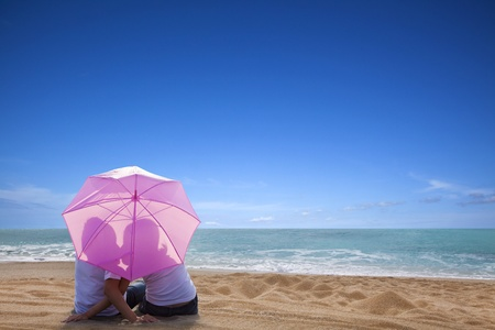 young couple romantic kissing at the beach with the umbrella photo