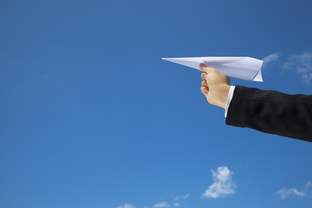 paper airplane: hand of Businessman letting an airplane made of paper fly over blue sky