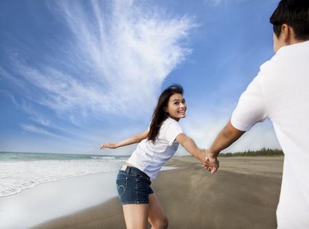 esposas: feliz pareja asi�tica que se ejecutan en la playa Foto de archivo