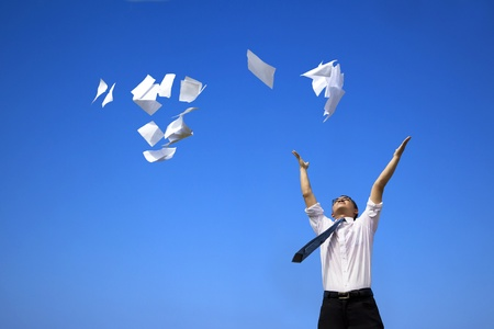 flying man: business man relaxing and throwing white papers  to the blue sky