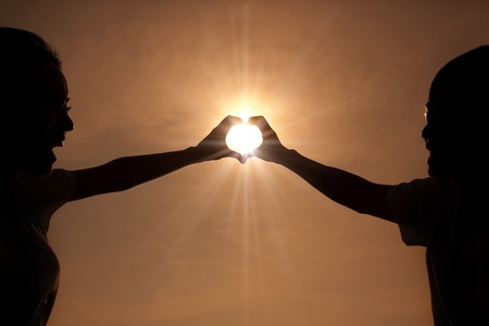 happy young couple making heart shape with hands  at sunset photo