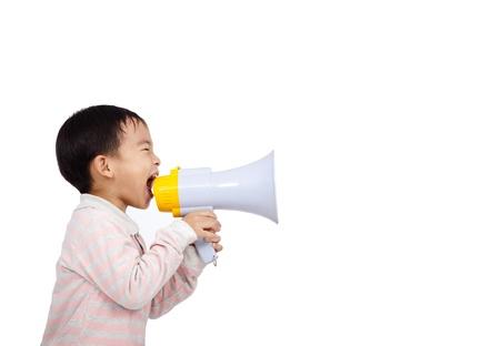 niños platicando: chico asiático grita algo en el megáfono Foto de archivo