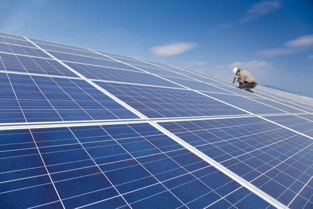 installer: close up solar panel and professional worker installing photovoltaic solar panels