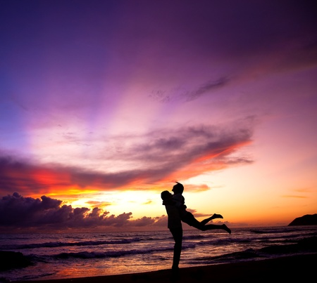 Silhouette of happy  couple embracing on the beach Standard-Bild