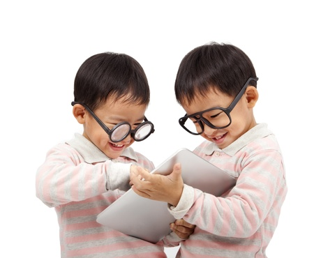 bambini cinesi: due bambini felici con computer touch pad e isolati su bianco