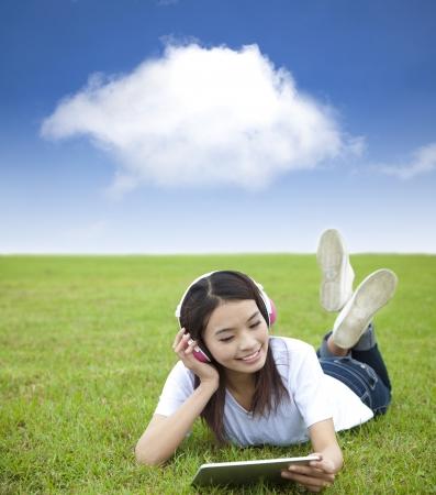 gelukkig meisje met touchpad computer met hoofdtelefoon op de weide