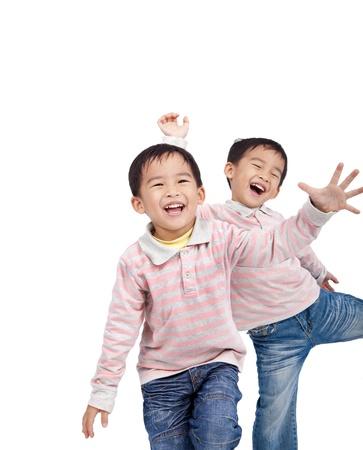 niños danzando: riendo pequeños niños asiáticos aislados sobre fondo blanco