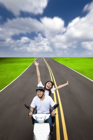 Happy couple having summer road trip on a scooter photo