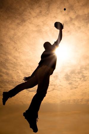 guante de beisbol: La silueta de jugador de b�isbol saltando en el aire para hacer la captura