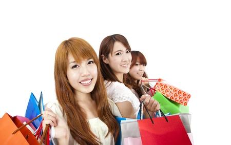 chicas comprando: tres mujeres j�venes con bolsa de la compra y aisladas sobre fondo blanco Foto de archivo