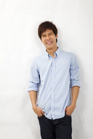 Happy smiling asian young man leaning against white wall photo