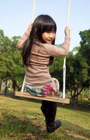 girl on swing: little girl on the swing Stock Photo